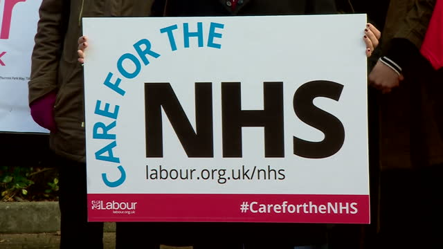 stockvideo's en b-roll-footage met exterior shots of labour campaigners posing with care for the nhs placards in front of a van with a billboard carrying the slogan nhs funding... - labor partij