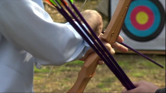 stockvideo's en b-roll-footage met exterior shots of labour leader jeremy corbyn mp trying his hand at archery whilst visiting a youth activity centre and signing autographs for young... - labor partij