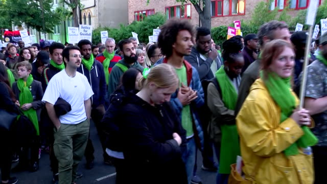 stockvideo's en b-roll-footage met exterior shots of labour leader jeremy corbyn taking part in a protest march on the anniversary of the grenfell tower fire wearing a green scarf... - stille