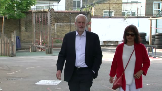 stockvideo's en b-roll-footage met exterior shots of labour leader jeremy corbyn with wife laura alvarez entering and leaving an islington polling station to cast votes in the european... - britse labor partij