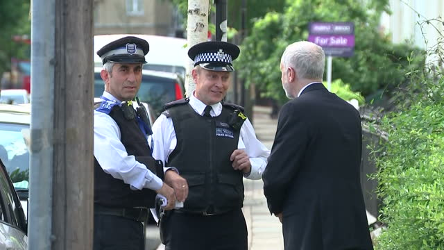 Exterior shots of Labour party leader Jeremy Corbyn walking along the street and stopping to speak to a police officer and another uniformed man on...