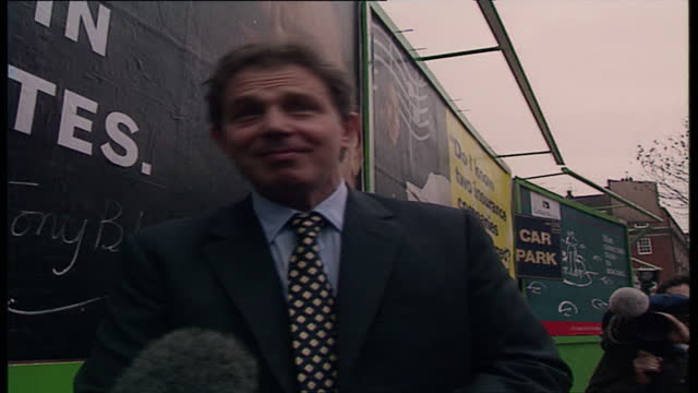 Exterior shots of Labour Party Leader Tony Blair signing Labour Party's new political poster and giving an interview to press about the poster slogan...