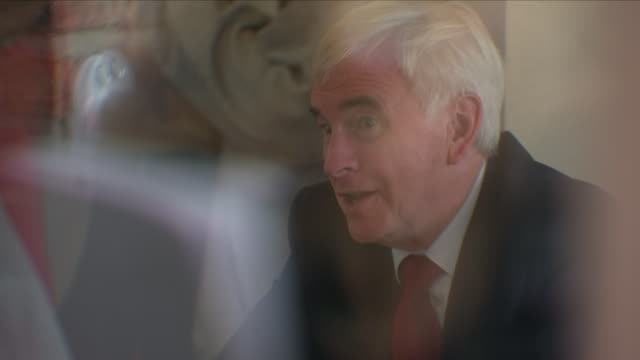 Exterior shots of Labour shadow chancellor John McDonnell and Labour leader Jeremy Corbyn visible through window chatting to Hillingdon Labour Party...