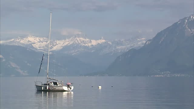 Exterior shots of Lake Geneva surrounded by picturesque mountains and boats sailing on May 17 2016 in Lausanne Switzerland