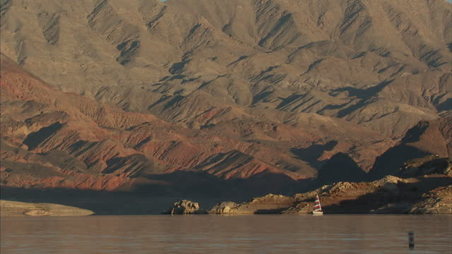 exterior shots of lake mead nevada with speedboat and sailing boat crossing it on december 12 2010 in las vegas nevada - lake mead video stock e b–roll