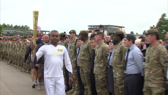 exterior shots of lance corporal johnson beharry, the youngest victoria cross recipient, carrying the olympic torch from the national memorial... - national memorial arboretum stock videos & royalty-free footage