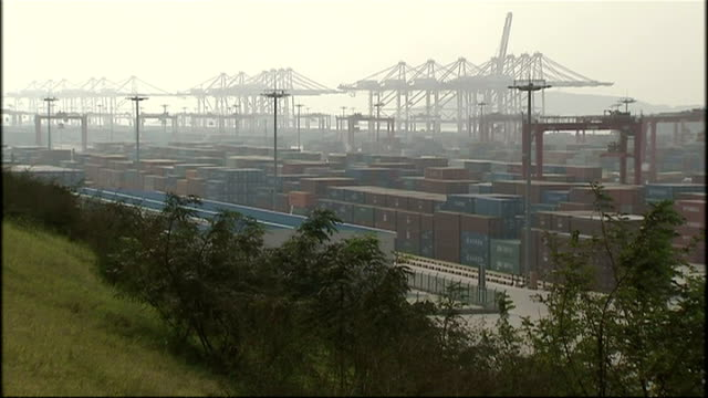 exterior shots of large cranes, containers and lorries moving around a deep water shipping port in shanghai on october 21, 2008 in shanghai, china. - film container stock videos & royalty-free footage