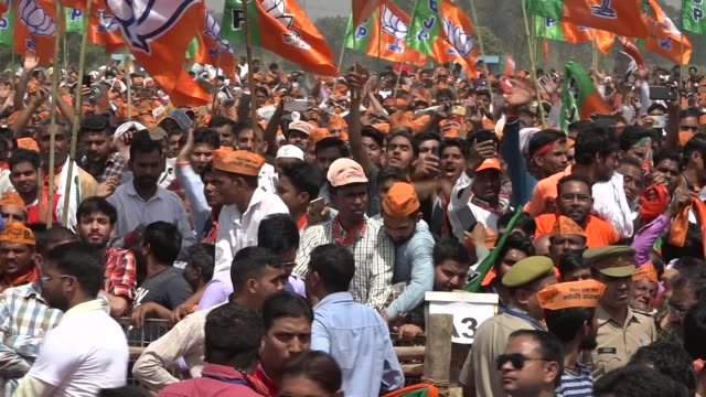exterior shots of large crowds of cheering bjp supporters waving large party flags and chanting cheering during a speech by prime minister narendra... - governmental occupation stock videos & royalty-free footage