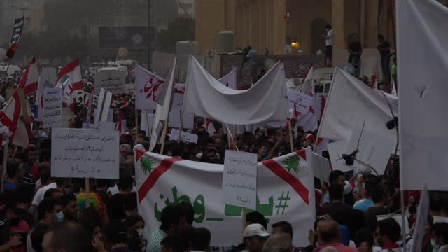 Exterior shots of large crowds of protesters in Martyrs Square in the centre of Beirut holding anti government placards and chanting at a mass rally...