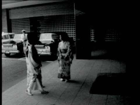 vídeos de stock, filmes e b-roll de exterior shots of large new hotels / hotel lift girls dressed in kimonos / ornamental pond beside new hotel / interior of hotel japanese girls... - 1964