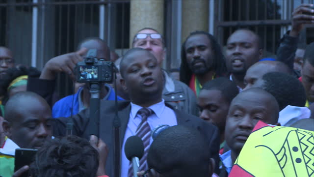 exterior shots of lawyer supporting pastor evan mawarire asking protesters outside of court to be quiet whilst they protest the pastor's imprisonment... - pastor stock videos & royalty-free footage