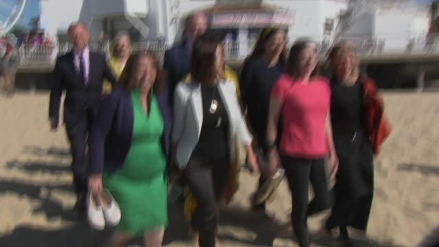 exterior shots of liberal democrat party members walking onto bournemouth beach. party members include: jo swinson, chuka umunna, tim farron,... - british liberal democratic party stock videos & royalty-free footage