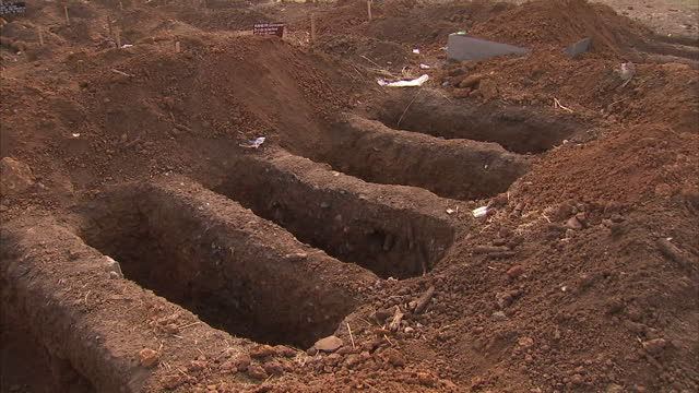 Exterior shots of lines of freshly dug graves in a rural part of Sierra Leone destined for the bodies of Ebola victims on January 12 2015 in Freetown...