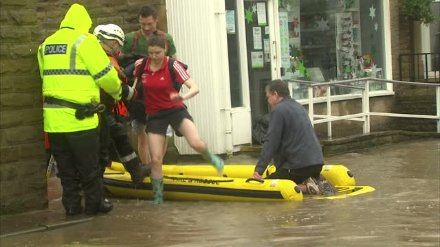 Exterior shots of local people being rescued by a fire and rescue crew from flood waters in an inflatible boat in Whalley Lancashire on December 27...