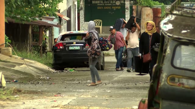 exterior shots of local people carrying their belongings making their way back to their houses in destroyed marawi city after its liberation from... - terrorism stock videos & royalty-free footage