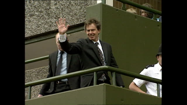 vídeos y material grabado en eventos de stock de exterior shots of local people waiting to catch a glimse of prime minister tony blair as he visits the aylesbury estate and tony blair waving from a... - grounds