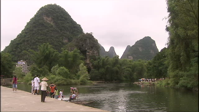 Exterior shots of local residents sailing on the Yulong river on bamboo rafts surrounded by iconic limestone mountainous peaks on September 1 2008 in...
