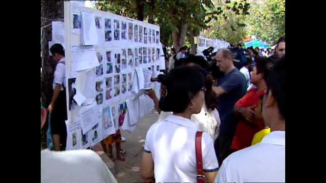 exterior shots of locals and tourists looking at notice boards with details of people missing in the aftermath of the asian tsunami in phuket>> on... - 2004 stock-videos und b-roll-filmmaterial