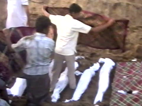 exterior shots of locals burying victims of tsunami wave in mass burial grave ceremony family members crying and upset at what has heppened boxing... - 2004年点の映像素材/bロール
