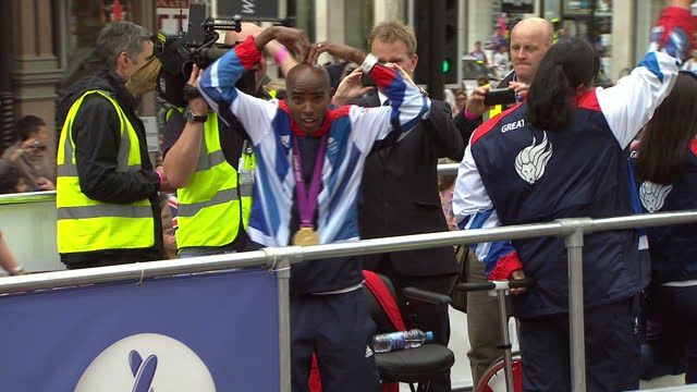 exterior shots of london 2012 parade with mo farah on bus performing mobot with lion float moving along in parade and beth tweddle on bus with team... - parade float stock videos and b-roll footage