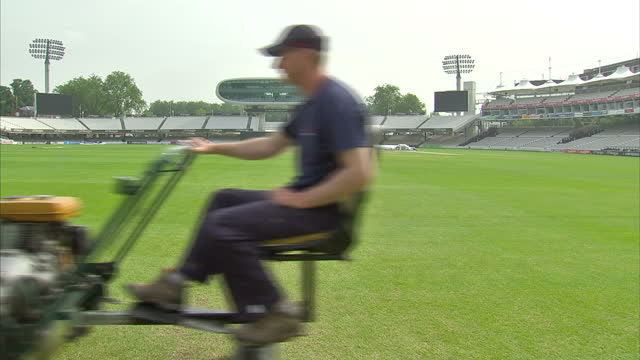 exterior shots of lord's cricket ground in st john's wood view of ground from road also man sitting on lawn mower mowing grass lord's cricket ground... - lords cricket ground stock videos and b-roll footage