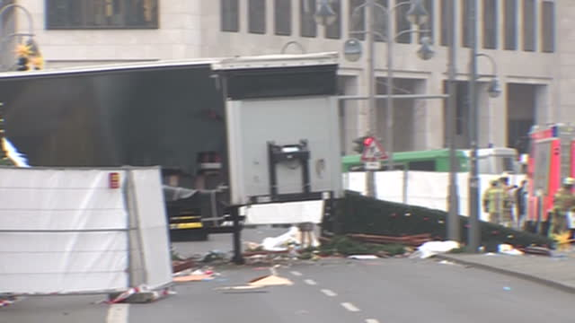 exterior shots of lorry that ploughed into berlin christmas market in terror attack being towed away and scene being fenced off by emergency workers... - terrorism stock videos & royalty-free footage