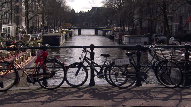 Exterior shots of lots of cyclists in the heart of Amsterdam over bridges and alongisde canals barges passing along a canal and the Westerkerk Church...