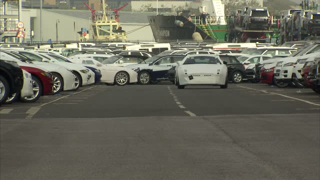 exterior shots of luxury cars at southampton dock waiting to board a cargo ship including range rover evoques jaguars and heavy industrial cat dump... - southampton england stock videos and b-roll footage