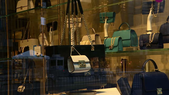 exterior shots of luxury goods stores on new york's fifth avenue including a harry winston window display featuring a large golden cockerel motif... - borsetta video stock e b–roll