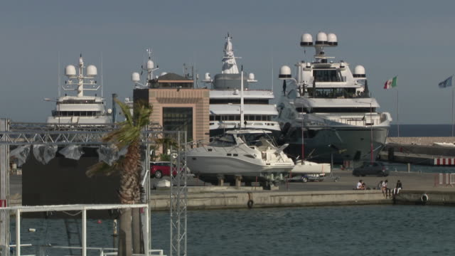 vidéos et rushes de exterior shots of luxury yachts around san remo's harbour area including sir philip green's 'lionheart' and high shots of people playing tennis on a... - millionnaire