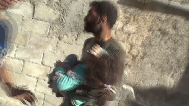 vídeos de stock, filmes e b-roll de exterior shots of man running with little girl who was pulled out from rubble in his arms and get into back of ambulance in the aftermath of an... - dano físico