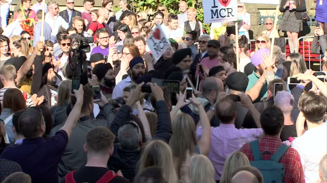exterior shots of manchester terror attack vigil in albert square with a group of sikh men arriving holding i love manchester signs on 23rd may 2017... - manchester arena stock videos & royalty-free footage