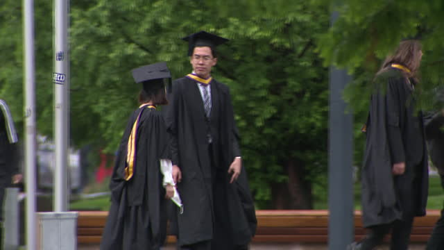 """exterior shots of manchester university campus, with graduates in hats and gowns walking around and a coat of arms reading """"olim armis nunc studiis""""... - cap stock videos & royalty-free footage"""