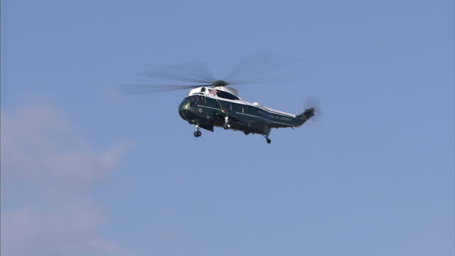 vídeos de stock e filmes b-roll de exterior shots of marine one and two flying past the washington monument possibly carrying barack obama on january 16 2016 in washington dc - cemitério nacional de arlington