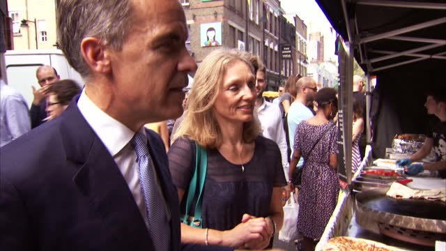 Exterior shots of Mark Carney Governor of the Bank of England walking up to a street food market stall and hand the vendor a new £5 note on September...