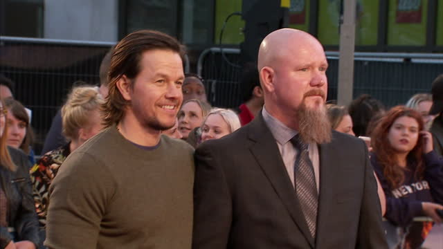 Exterior shots of Mark Wahlberg and Mike Williams posing for photos on the red carpet at the premiere of Deepwater Horizon at Leicester Square on...