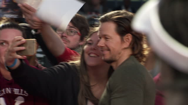 Exterior shots of Mark Wahlberg taking selfies with fans on the red carpet at the premiere of Deepwater Horizon at Leicester Square on September 26...