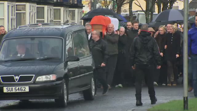 Exterior shots of Martin McGuinness' coffin being carried through the Bogside area of Derry draped with the Irish tricolour at the head of a large...