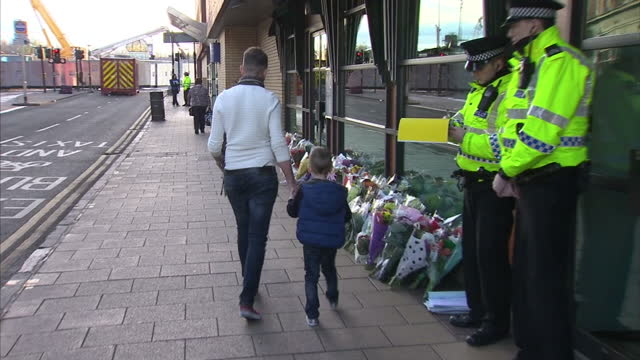 exterior shots of members of the public and police laying floral tributes near where a police helicopter crashed into a pub in glasgow investigation... - ヘリコプター事故点の映像素材/bロール