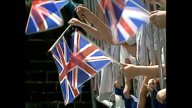 vídeos de stock, filmes e b-roll de exterior shots of members of the public waiting for princess diana's arrival and police band performing at the merseyside police training centre on... - princesa diana