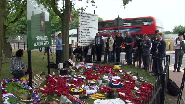 exterior shots of memorial service at the royal artillery barracks floral tributes laid on floor soldiers standing in group people holding flowers... - ウールウィッチ点の映像素材/bロール