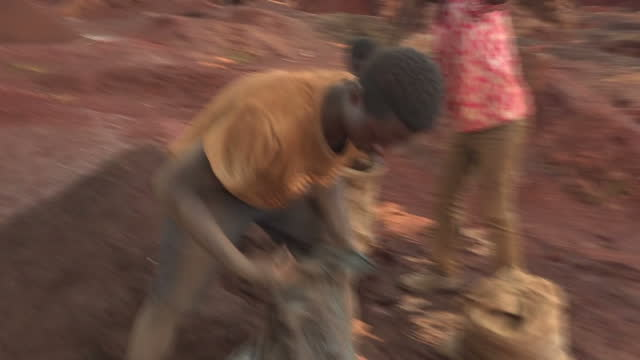 vídeos de stock e filmes b-roll de exterior shots of men & children filling sacks with ore at a cobalt mining area on february 10, 2017 in democratic republic of congo. - mina de carvão