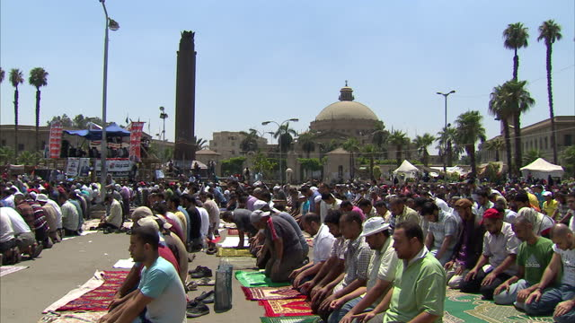 exterior shots of men gathered and taking part in midday prayer before pro mohamed morsi supporters chanting and waving egypt flags pro morsi... - midday stock videos and b-roll footage