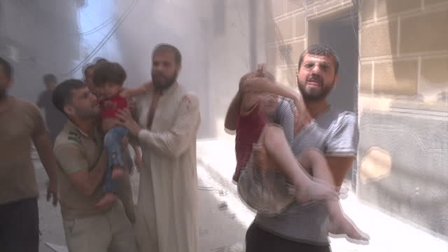 Exterior shots of men pulling children out of buildings that have been hit by an air strike on August 18 2016 in Aleppo Syria