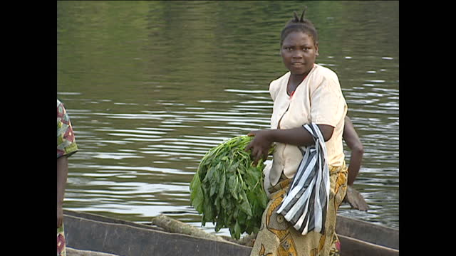 Exterior shots of men stood on wooden boats rowing to the banks women with groceries and people buying goods from a village stall on August 21 2001...