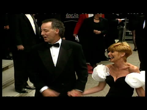 vidéos et rushes de exterior shots of michael barrymore and wife jennifer arriving at the bafta awards posing for photo ops signing autographs before entering building - autographe
