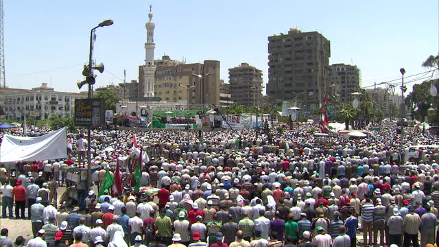 exterior shots of midday prayers for muslim brotherhood supporters close ups of president mohamed morsi's face on posters and people praying midday... - midday stock videos and b-roll footage