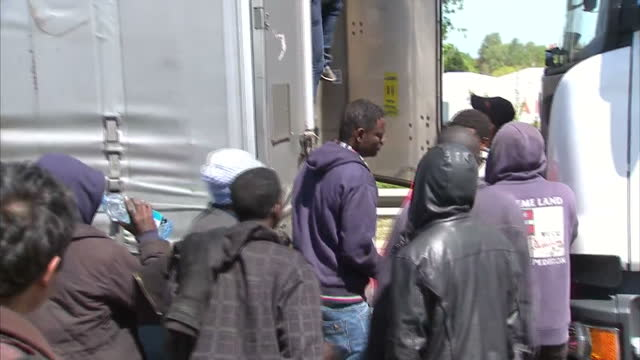 exterior shots of migrant observing lorry exterior shots of police officer opening doors of back of lorry and migrants get out of lorry on may 13... - calais stock videos & royalty-free footage