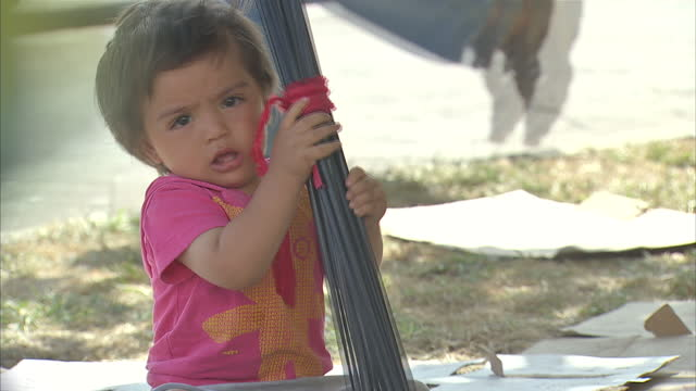 exterior shots of migrant refugee children in lesbos greece a baby wearing pink clothing and a nappy sleeps on a small pink blanket at the side of... - wearing a towel stock videos and b-roll footage