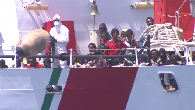 exterior shots of migrants on an italian coastguard rescue boat, after being rescued from the mediterranean sea which departed from libyan shores.... - migrazione animale video stock e b–roll